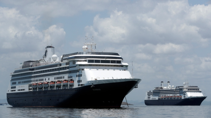 The Zaandam cruise ship, left, carrying some guests with flu-like symptoms, is anchored shortly after it arrived to the bay of Panama City, Friday, March 27, 2020, amid the worldwide spread of the new coronavirus. (AP Photo/Arnulfo Franco)