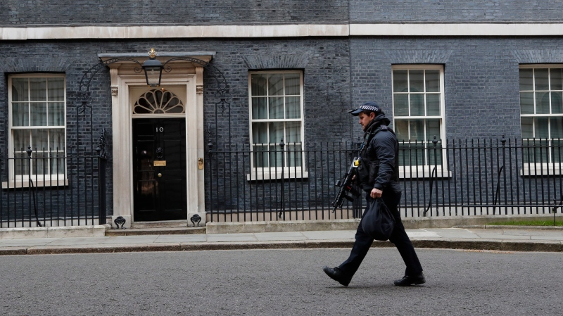 A police officer walks in Downing Street in London after it was announced that British Prime Minister Boris Johnson has tested positive for the new coronavirus, Friday, March 27, 2020. (AP Photo/Frank Augstein)