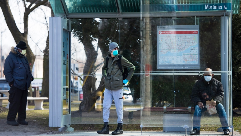 People wear masks while sitting in a bus shelter in Toronto on Friday, March 27, 2020. People are taking extra measures against the spread of the coronavirus also known as COVID-19. THE CANADIAN PRESS/Nathan Denette