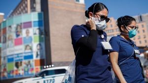Nurses leave Elmhurst Hospital Center where COVID-19 testing continues outside, Friday, March 27, 2020, in New York. The new coronavirus causes mild or moderate symptoms for most people, but for some, especially older adults and people with existing health problems, it can cause more severe illness or death. (AP Photo/John Minchillo)