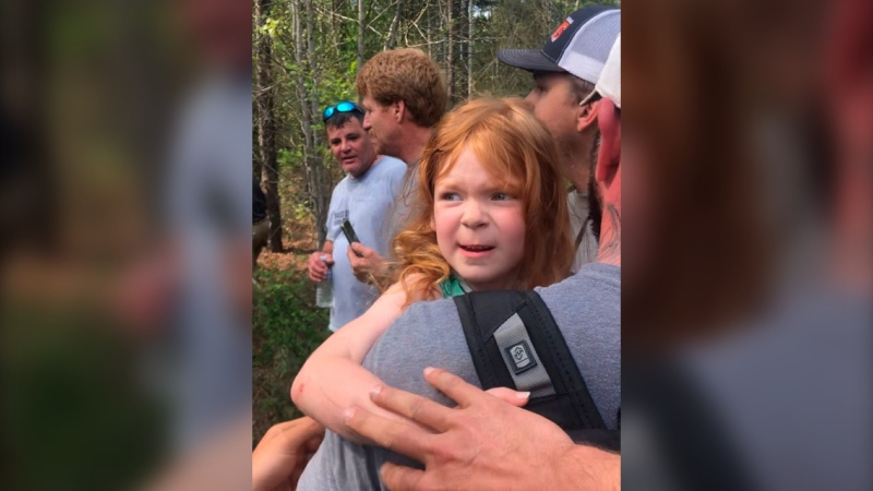 In a photo provided by Clay Carson, rescuers carry four-year-old Vadie Sides out of the woods in Lee County, Ala., Friday, March 27, 2020. (Clay Carson via AP)