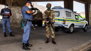 A policeman and soldier man a roadblock in Cape Town, South Africa, Friday, March 27, 2020, after South Africa went into a nationwide lockdown for 21 days in an effort to mitigate the spread to the coronavirus. (AP Photo)
