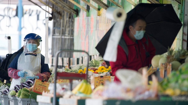 Both workers and shoppers take precautions by using face masks and social distancing to stay safe from COVID-19 at a produce market in Vancouver Friday, March 27, 2020. THE CANADIAN PRESS/Jonathan Haywar