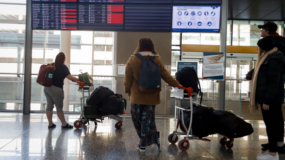Passengers look a board with cancelled flights at the Calgary Airport in Calgary, Alta., Wednesday, March 25, 2020, amid a worldwide COVID-19 flu pandemic. THE CANADIAN PRESS/Jeff McIntosh