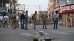 Indian policemen stand guard on a road during lockdown in Hyderabad, India, Saturday, March 28, 2020. Indian Prime Minister Narendra Modi announced a 21-day lockdown that began on Wednesday and effectively put millions of Indians who live off daily earnings out of work. India's finance ministry announced a 1.7 trillion ($22 billion) economic stimulus package that will include delivering grains and lentil rations for three months to 800 million people, around 60% of the world's second-most populous country. (AP Photo/Mahesh Kumar A.)