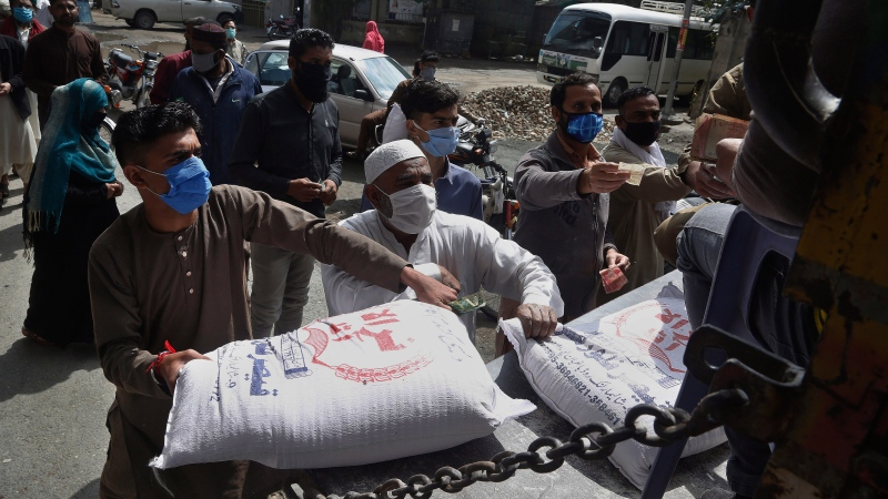 People buy wheat flour from a governmental subsidized sale point during lockdown, in Lahore, Pakistan, Saturday, March 28, 2020. (AP Photo/K.M. Chaudary)