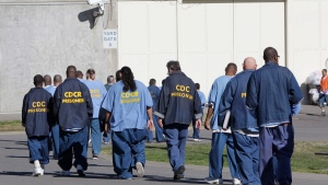 In this Feb. 26, 2013, file photo, inmates walk through the exercise yard at California State Prison Sacramento, near Folsom, Calif. Public interest attorneys filed an emergency motion, Wednesday, March 25, 2020, asking federal judges to free thousands of infirm and lower-security California prison inmates to prevent a spread of the coronavirus. (AP Photo/Rich Pedroncelli, File)