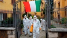 Workers wearing protective outfits sanitize a neighborhood to contain the spread of Covid-19 virus, in Rome, Saturday, March 28, 2020. The new coronavirus causes mild or moderate symptoms for most people, but for some, especially older adults and people with existing health problems, it can cause more severe illness or death. (Mauro Scrobogna/LaPresse via AP)