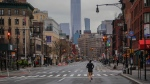 In this file photo, a lone jogger runs on a partially empty 7th Avenue, resulting from citywide restrictions calling for people to stay indoors and maintain social distancing in an effort to curb the spread of COVID-19, Saturday March 28, 2020, in New York. (AP Photo/Bebeto Matthews)