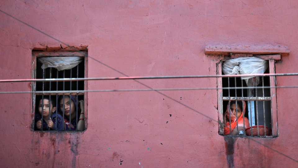 A family looks out from the window of his house in the old quarters of Delhi following a lockdown amid concern over spread of coronavirus, India, Friday, March 27, 2020. (AP Photo/Manish Swarup)