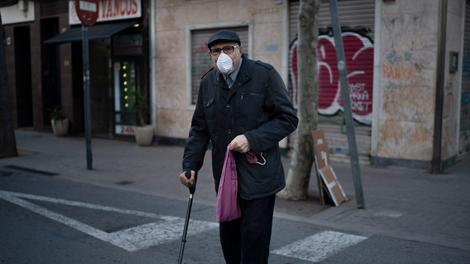 An elderly man wearing a face mask walks home from the bakery as the lockdown to combat the spread of coronavirus continues in Badalona, Spain, Friday, March 27, 2020. The new coronavirus causes mild or moderate symptoms for most people, but for some, especially older adults and people with existing health problems, it can cause more severe illness or death. (AP Photo/Felipe Dana)