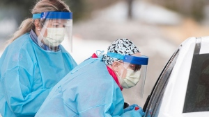 Healthcare workers talk to a driver before issuing a test at a drive-thru COVID-19 evaluation clinic in Montreal, Sunday, March 29, 2020, as Coronavirus COVID-19 cases rise in Canada and around the world. THE CANADIAN PRESS/Graham Hughes