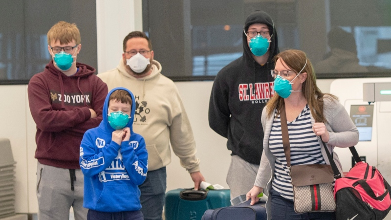 Travellers wear masks as they walk through Trudeau Airport Friday, March 13, 2020 in Montreal. THE CANADIAN PRESS/Ryan Remiorz