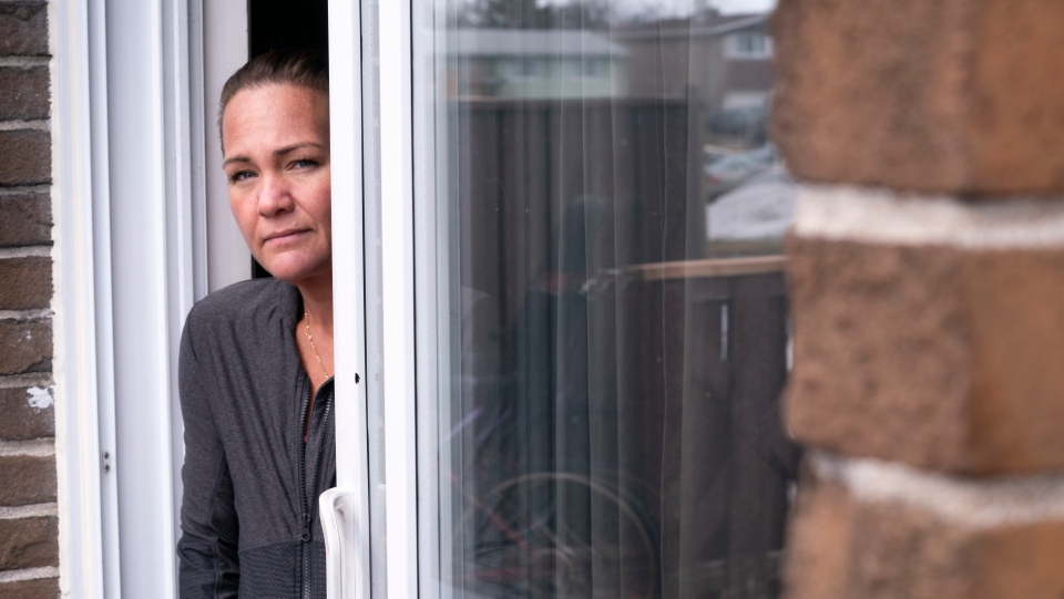 Melanie Fournier, who has contracted the COVID-19 virus, peers out the patio door of her home in Montreal on Thursday, March 26, 2020. THE CANADIAN PRESS/Paul Chiasson