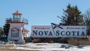 Travellers are greeted as they arrive in Nova Scotia near Amherst, N.S. on Sunday, March 22, 2020. Premier Stephen McNeil announced anyone entering Nova Scotia, apart from those deemed essential workers, must now self-isolate for 14 days. THE CANADIAN PRESS/Andrew Vaughan