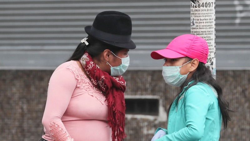 Street vendors, wearing protective face masks and disposable gloves as a precaution against the spread of the new coronavirus, wait for customers on a street corner in Quito, Ecuador, Saturday, March 28, 2020. (AP Photo/Dolores Ochoa)