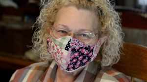 In this Tuesday, March 24, 2020 photo, semi-retired nurse Sara Morrison models a mask she sewed at her home in St. Albans, W.Va., making masks on her sewing machine for health care workers at Charleston Area Medical Center. (Chris Dorst/Charleston Gazette-Mail via AP)