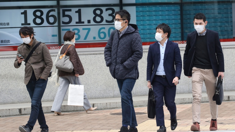People walk by an electronic stock board of a securities firm in Tokyo, Monday, March 30, 2020. (AP Photo/Koji Sasahara)