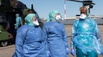 Medical staffs walk on the tarmac of the Strasbourg airport as they evacuate a patient infected with the Covid-19 virus into a French military helicopter heading to Switzerland to ease the situation in eastern France, Monday, March 30 2020 in Strasbourg, eastern France. The new coronavirus causes mild or moderate symptoms for most people, but for some, especially older adults and people with existing health problems, it can cause more severe illness or death. (AP Photo/Jean-Francois Badias)