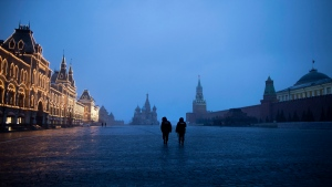 Two police officers patrol an almost empty Red Square, with St. Basil's Cathedral, center, and Spasskaya Tower and the Kremlin Wall, right, at the time when its usually very crowded in Moscow, Russia, Monday, March 30, 2020. Russian President Vladimir Putin says the country has managed to slow down the spread of coronavirus but should be prepared for contagions to quickly grow. (AP Photo/Alexander Zemlianichenko)