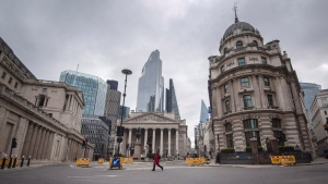 A woman walks through a deserted Bank junction as the U.K. continues in lockdown to help curb the spread of the coronavirus, in London, Monday March 30, 2020. (Victoria Jones/PA via AP)