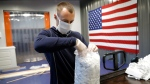 In this Thursday, March 26, 2020 photo, A.J. Davidson, who works in the business development department at Blue Delta Jeans, packages face guards made at the jeans manufacturing site in Shannon, Miss. The company has shifted its operation from making custom jeans to help with the demand of face masks to combat the coronavirus outbreak. The new coronavirus causes mild or moderate symptoms for most people, but for some, especially older adults and people with existing health problems, it can cause more severe illness or death. (AP Photo/Julio Cortez)