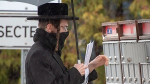 A member of the Tosh de Boisbriand community gets his mail Monday, March 30, 2020 in Boisbriand, Que. north of Montreal. Quebec public health authorities have placed the community of around 4,000 orthodox Jews in the Laurentians under quarantine after a number of members tested positive for COVID-19.THE CANADIAN PRESS/Ryan Remiorz