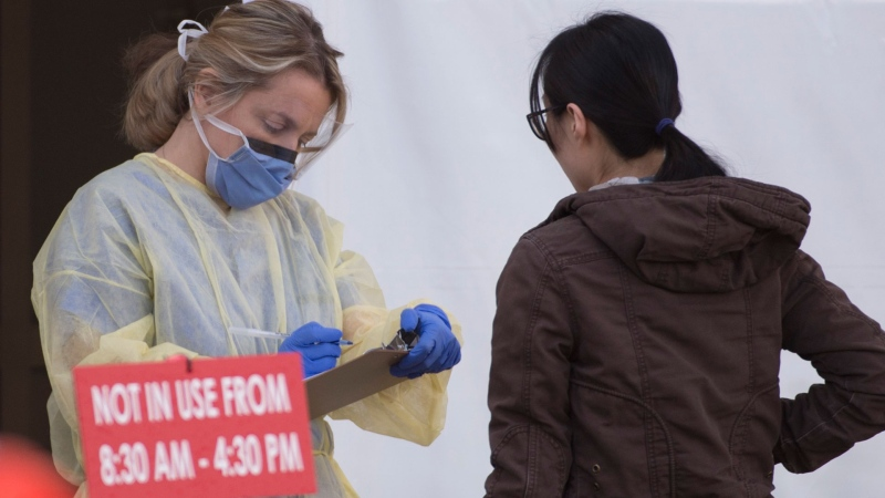 A hospital worker is seen at the staff assessment area outside the Lions Gate Hospital in North Vancouver, B.C. Monday, March 23, 2020. THE CANADIAN PRESS/Jonathan Hayward