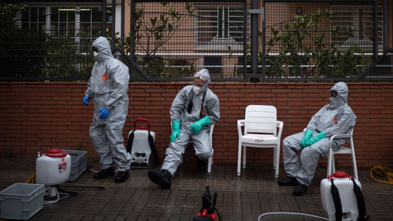 Firefighters wearing protective suits wait outside a nursing home before disinfecting it in efforts to prevent the spread of the new coronavirus in Barcelona, Spain, Monday, March 30, 2020. The new coronavirus causes mild or moderate symptoms for most people, but for some, especially older adults and people with existing health problems, it can cause more severe illness or death. (AP / Felipe Dana)