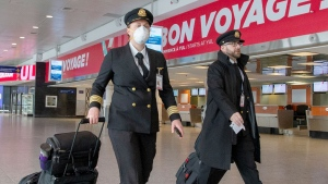 Airline personnel walk through a deserted Trudeau airport, Monday March 30, 2020 in Montreal.THE CANADIAN PRESS/Ryan Remiorz