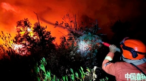 In this Monday, March 30, 2020 photo, a firefighter battles a forest fire as it approaches a gas station in Xichang in southwestern China's Sichuan Province. (Chinatopix via AP)