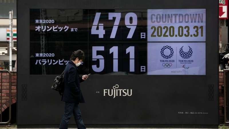 A man walks past a countdown display for the Tokyo 2020 Olympics and Paralympics Tuesday, March 31, 2020, in Tokyo. The clock read 479 days to go. (AP Photo/Jae C. Hong)