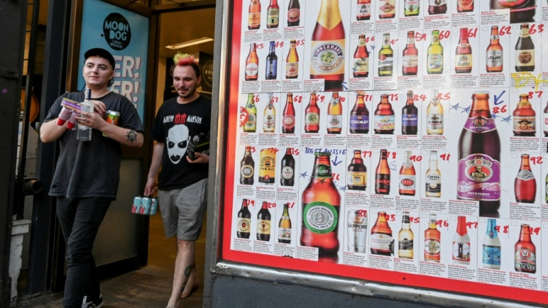 Two men leave a bottle shop in Melbourne after major alcohol retailers in Australia agreed to enforce new rules limiting individual purchases. (AFP)