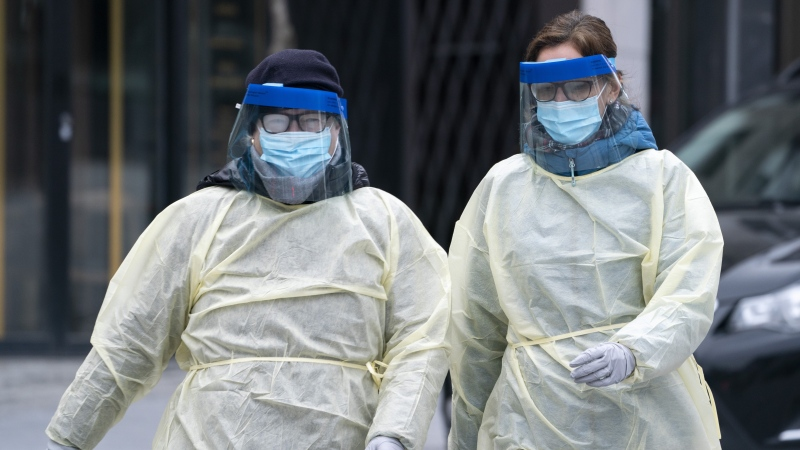 Two health care workers arrive at a walk-in COVID-19 test clinic in Montreal on March 23, 2020. THE CANADIAN PRESS/Paul Chiasson