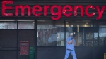 A health care worker is seen outside the Emergency dept. of the Vancouver General Hospital in Vancouver Monday, March 30, 2020. THE CANADIAN PRESS/Jonathan Hayward
