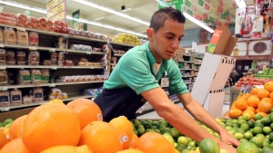 A grocery store worker restocks limes in the produce section.