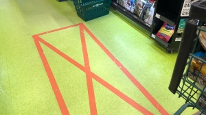 Tape on the floor of a Saskatoon grocery store marks the distance required between shoppers.
