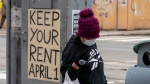 A woman walks past signs to withold rent in Toronto on Tuesday March 31, 2020. THE CANADIAN PRESS/Frank Gunn
