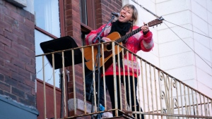 Singer Martha Wainwright entertains people from the balcony of her apartment in Montreal on Tuesday, March 31, 2020. THE CANADIAN PRESS/Paul Chiasson