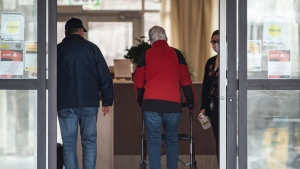 A staff member wearing a mask and holding sanitizer greets people entering a building at the Promenade retirement residence, where local health officials reported Ottawa's first case of COVID-19 in a retirement or long-term care home after a resident tested positive for the novel coronavirus, on Saturday, March 28, 2020. THE CANADIAN PRESS/Justin Tang