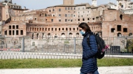 A woman walks past the Trajan's Forum in Rome, Tuesday, March 31, 2020. Italy observed a minute of silence and flown its flags at half-staff in a nationwide gesture to honor the victims of the coronavirus and their families. The new coronavirus causes mild or moderate symptoms for most people, but for some, especially older adults and people with existing health problems, it can cause more severe illness or death. (Cecilia Fabiano/LaPresse via AP)