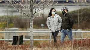 Pedestrians wear personal protective equipment while walking in Hunters Point South Park in the Queens borough of New York, on March 31, 2020. (Frank Franklin II / AP)
