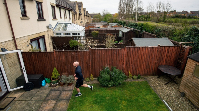 James Campbell runs a charity marathon to raise funds for the NHS, in his garden, while the country is in lockdown to control the spread of coronavirus, in Cheltenham, England, on April 1, 2020.  (Jacob King / PA via AP)