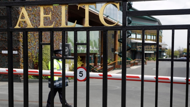 A security guard outside the main gates to Wimbledon as it is announced the the Wimbledon tennis Championships for 2020 has been cancelled due to the coronavirus in London, Wednesday, April 1, 2020. (AP Photo/Kirsty Wigglesworth)