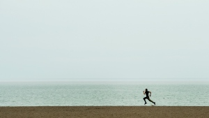 A lone man gets exercise at Woodbine Beach in Toronto on Thursday, March 26, 2020. (THE CANADIAN PRESS / Nathan Denette)