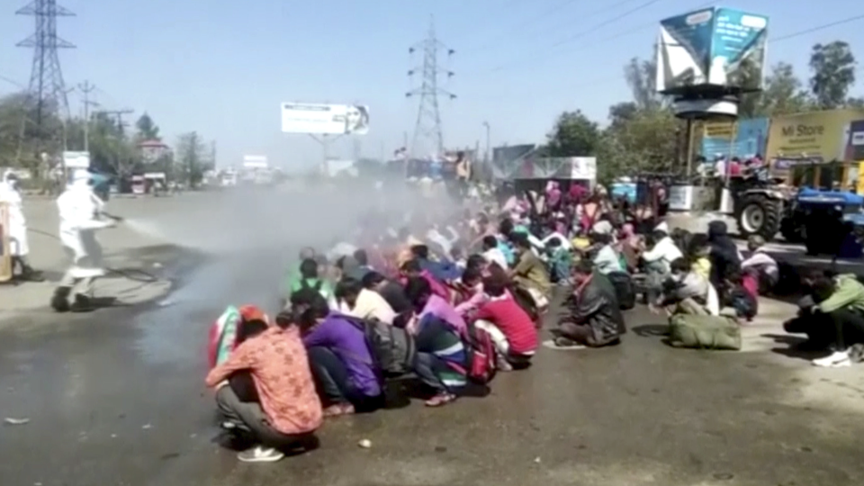 In this image made from video taken Sunday, March 29, 2020, and provided Wednesday, April 1, 2020, by Anoop Mishra, people in protective suit spray disinfectant over a group of people sitting down on ground in Bareilly in the northern state of Uttar Pradesh, India. (Anoop Mishra via AP)