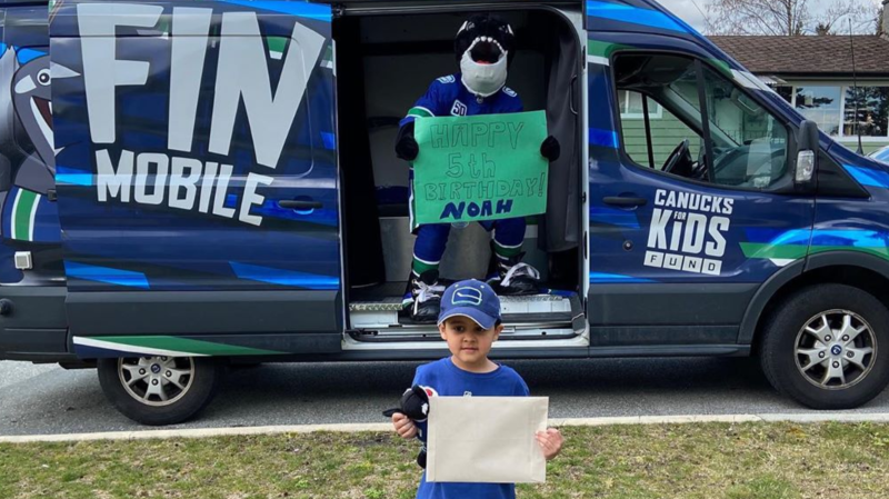 Noah poses at a distance from Vancouver Canucks mascot 'Fin' in a photo posted to an Instagram account set up for the mascot.