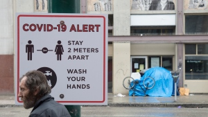 A man walks past a COVID-19 alert sign in Vancouver's Downtown Eastside on Thursday, March 26, 2020. THE CANADIAN PRESS/Jonathan Hayward