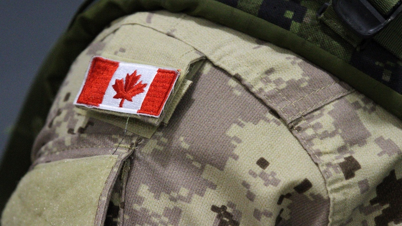 A Canadian flag patch is shown on the shoulder of a member of the Canadian forces in Trenton, Ont., on Thursday, Oct. 16, 2014. Canadian troops returning from Ukraine this month have not been told whether they will allowed to quarantine at home with their families or forced to spend the two weeks somewhere else. THE CANADIAN PRESS/Lars Hagberg