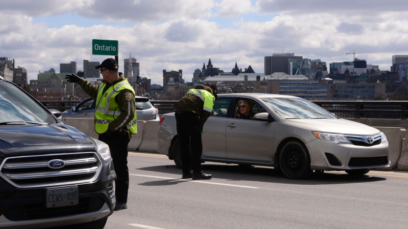 Quebec police officers randomly stop traffic entering Quebec from Ottawa on Wednesday, April 1, 2020, during the COVID-19 pandemic. THE CANADIAN PRESS/Sean Kilpatrick